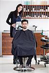 Ein Friseur mit einen Spiegel für Kunden
