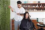 Eine Frau, die ihr Haar Schneiden von männlichen Friseur