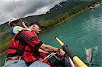 A mature couple catch a Dolly Varden while rafting on the Kenai River near Cooper Landing, Kenai Peninsula, Southcentral Alaska, Summer