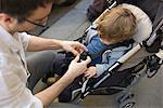Vater strapping Toddler Boy in Kinderwagen
