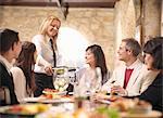 Waitress serving people in restaurant