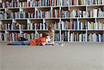 Children reading together by bookshelves