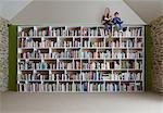 Children sitting on top of bookshelves