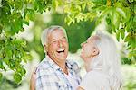 Senior couple laughing under tree