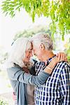 Senior couple hugging under tree
