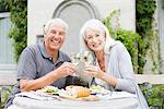 Couple senior, boire du vin à table de patio
