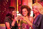 Friends toasting shot glasses in nightclub