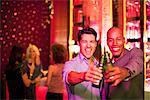 Männer Toasten Bierflaschen in Nachtclub