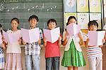 Enfants en classe de musique tenant Note