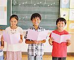 Enfants dans la Note de musique classe Holding et souriant