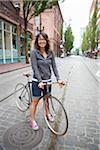 Femme avec vélo debout dans la rue