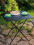An outdoor table in a   flowering garden, Sweden.