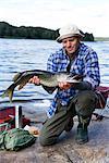 A man holding a pike, Sweden.