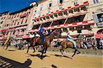 Riders racing at El Palio horse race festival, Piazza del Campo, Siena, Tuscany, Italy, Europe