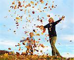 Père et fils, jouant dans les feuilles d'automne