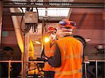 Arbeitnehmer tragen Mundschutz in Anlage