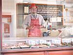 Butcher holding steak behind counter