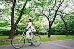 Eau potable de femme d'affaires tout en restant assis sur le vélo