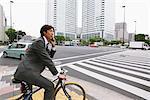 Homme d'affaires à l'aide de téléphone Mobile tout en cyclisme