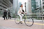 Femme d'affaires au transport sur bicyclette et gens d'affaires en arrière-plan