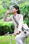 Eau potable de femme d'affaires tout en vélo