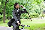Homme d'affaires eau potable tout en vélo