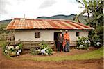 Burundi. A couple outside a traditional house on their farm.