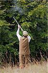 UK. Wiltshire. A man fires his shotgun at a driven partridge shoot.