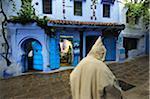 Man wearing a kaftan, walking along the bluish Chefchaouen medina. Morocco