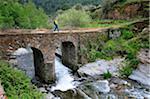 Woman walking along a medieval bridge. Las Hurdes, Spain