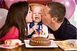 Eltern küssen Mädchen auf erste Geburtstagsfeier