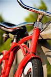 Image of red bike leaning against railing of boardwalk.