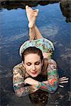 Sexy partially nude tattooed Caucasian woman lying in tidal pool in Maui, Hawaii, USA.