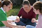 Three teen girls gathered outdoors to pray.