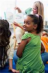 Kindergarten teacher reading to children in library, girl lookin