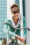 female commuter locking padlock to her bike.