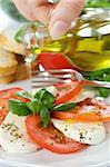 Oil over caprese salad with tomato and mozzarella