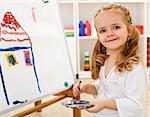 Little smiling artist girl proud of her work