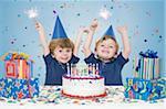 Zwei jungen halten Wunderkerzen mit Geburtstagskuchen und Geschenke
