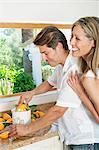 Couple à l'aide d'un presse-agrumes en cuisine