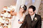 Couple de jeunes mariés avec sparkler sur gâteau