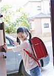 Girl waving hand at front door