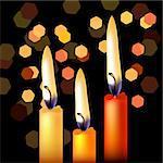 Three festive candles on night black background
