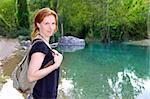 Hiker woman smiling backpack nature river lake trees redhead