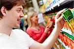 Portrait of happy guy choosing pack of juice in supermarket