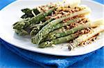 Asparagus gratin on white plate on blue background