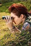 Attractive tattooed Caucasian woman lying on grass looking through binoculars in Maui, Hawaii, USA.