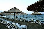 A row of empty sunchairs with beach umbrellas.