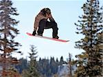 Teen girl jumping high on a snowboard