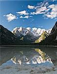 Lago di Landro reflecting the snowy Cristallo Mountains in the still morning air.